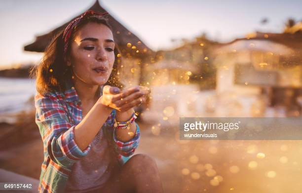 Aantrekkelijke jonge vrouw glitter waait op strand in de zomer