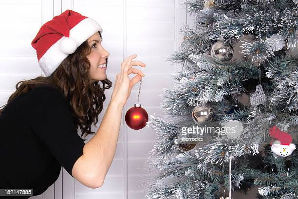 Attractive Young Woman Decorating Christmas Tree