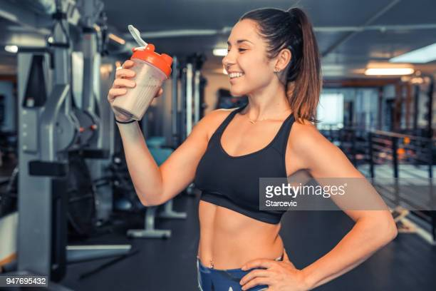 attractive young woman drinking protein shake at gym - protein drink stock pictures, royalty-free photos & images