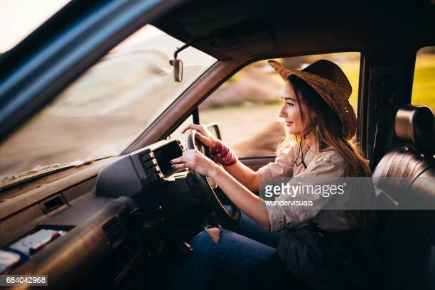 Aantrekkelijke jonge vrouw een vintage pick-up truck rijden