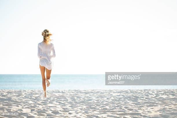 belle jeune femme dégustant une journée à la plage - femme blonde en maillot de bain vue de dos photos et images de collection
