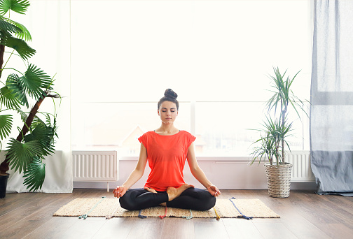 Attractive young woman exercising and sitting in yoga lotus position while resting at home 1156263061