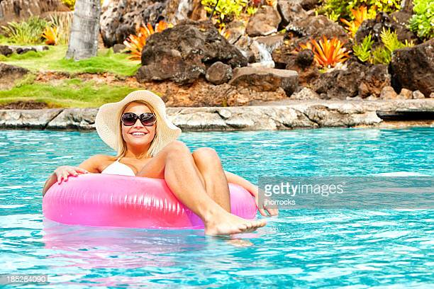 Attractive Young Woman Floating on Inner Tube Pool Toy