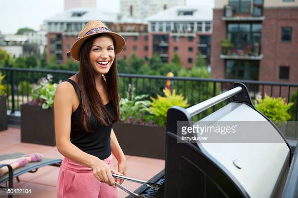 attractive young woman grilling - balcony stock pictures, royalty-free photos & images
