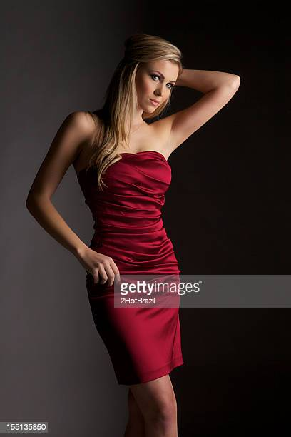 attractive young woman in a tight red dress - too small stock pictures, royalty-free photos & images