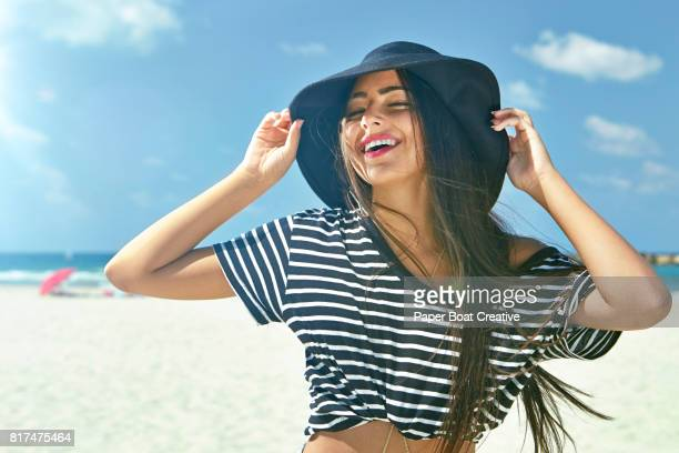 attractive young woman in black hat and striped shirt with bare midriff standing with arms up at the beach on a hot summer day - hot arab women stock photos and pictures