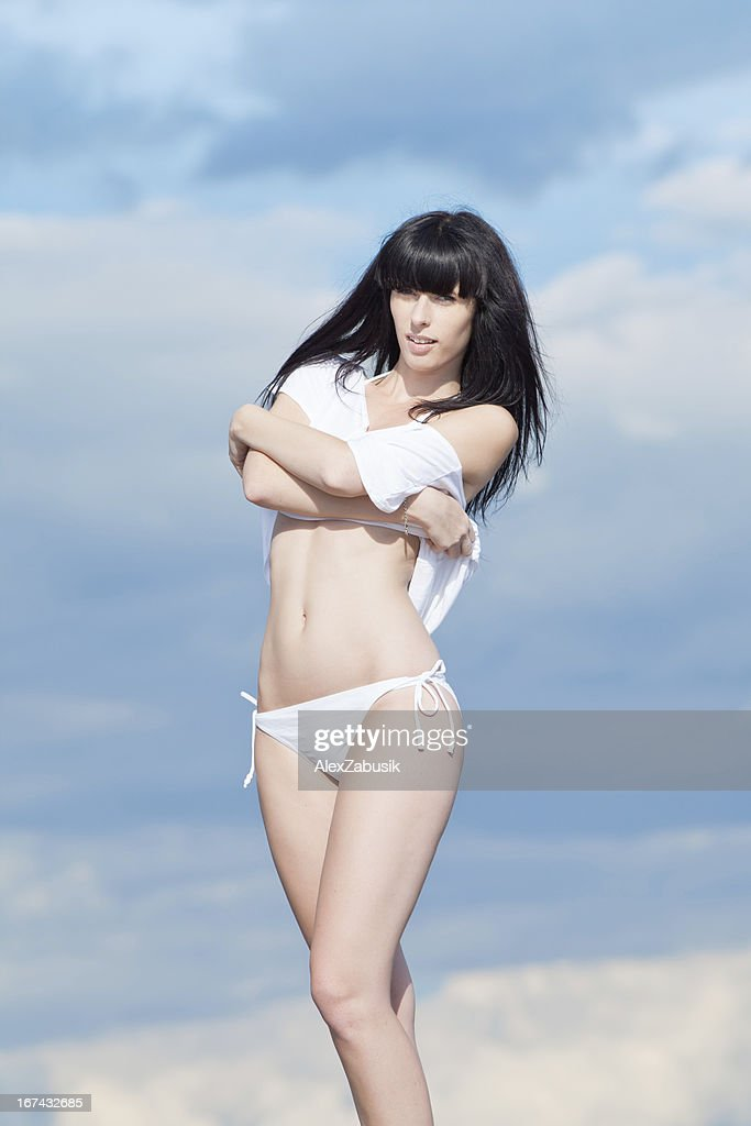 Mulher jovem atraente em Branco sobre fundo de céu nublado : Foto de stock