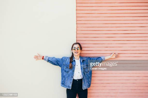 attractive young woman laughing on a two-colored wall - bras humain photos et images de collection