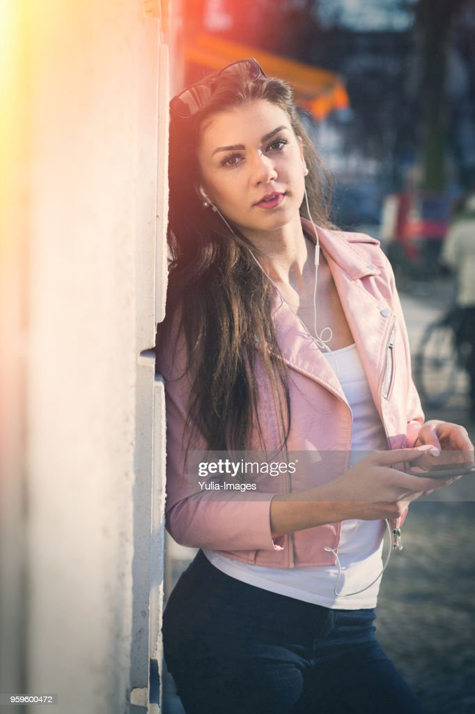 Attractive young woman listening to music in town : Stock-Foto