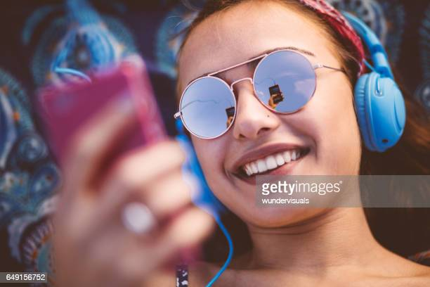 attractive young woman listening to music on her smart phone - upload stock pictures, royalty-free photos & images
