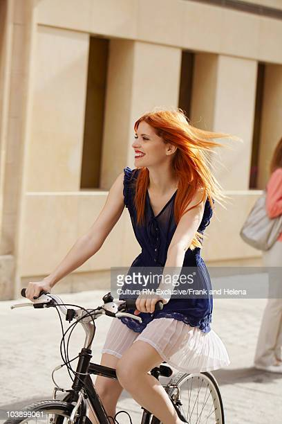 Attractive young woman on bike in street