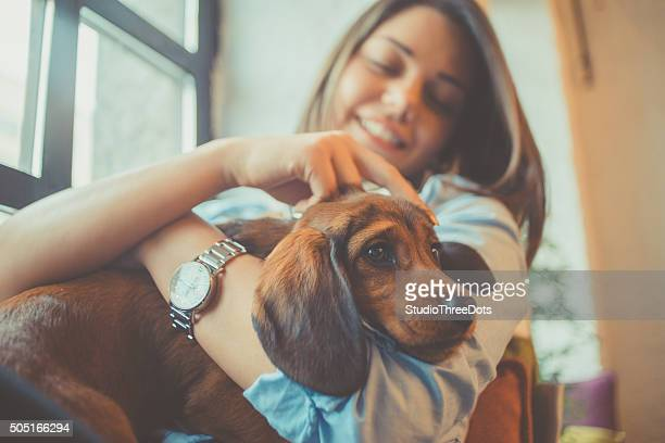 attractive young woman playing with puppy