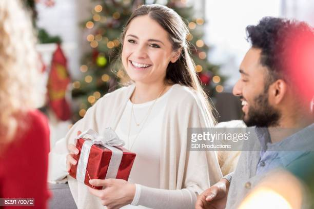 Attractive young woman prepares to open Christmas gift