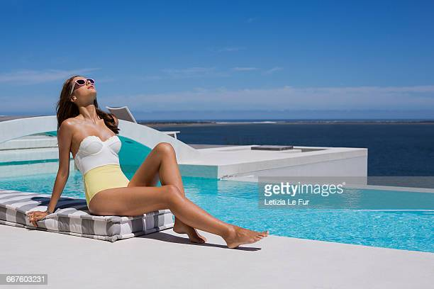 attractive young woman relaxing at the poolside - one piece swimsuit stock pictures, royalty-free photos & images