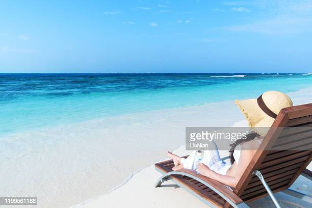 attractive young woman relaxing on the lounge chair with champagne -- tropical beach holiday and vacation copy space scene - liu he stock pictures, royalty-free photos & images