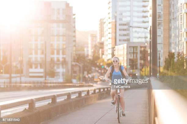 Attraktive junge Frau fährt Rad auf Bürgersteig an einem sonnigen Nachmittag