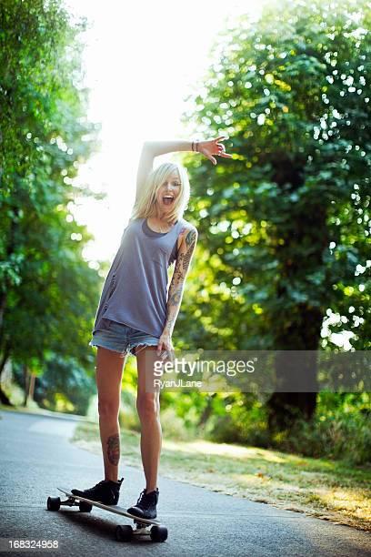 Attraktive junge Frau Reiten Longboard
