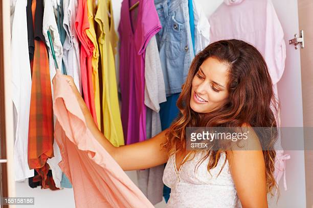 Attractive young woman selecting an outfit from her wardrobe