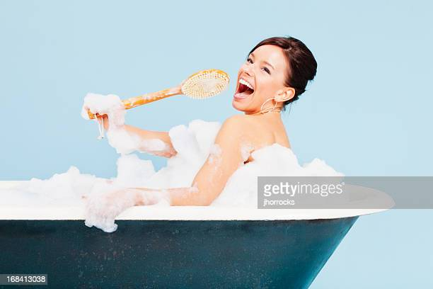 Attractive Young Woman Singing in Bath Tub