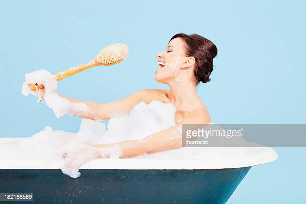 Attraktive junge Frau singt in Badewanne