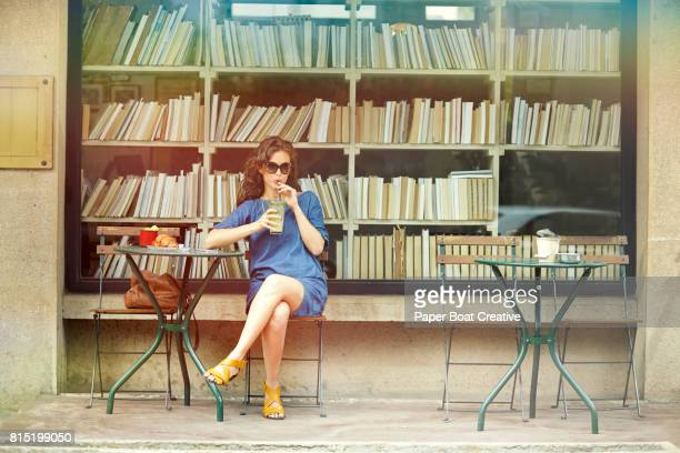 attractive young woman sipping juice sitting at an outdoor cafe table in front of a booktore with books on shelves behind her - café de calçada - fotografias e filmes do acervo