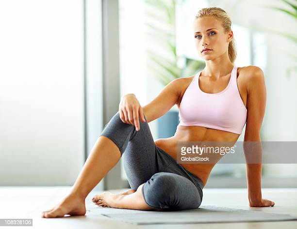 attraente giovane donna seduta in abbigliamento sportivo - donne bionde scalze foto e immagini stock