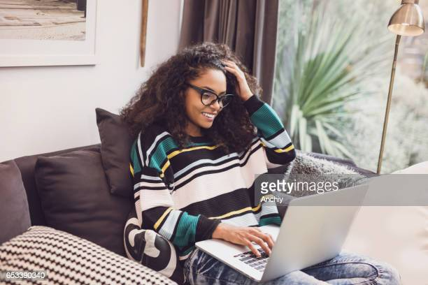 Attractive young woman sitting in the sofa with her laptop