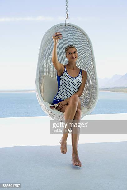 Attractive young woman sitting in wicker swing taking selfie with a smart phone