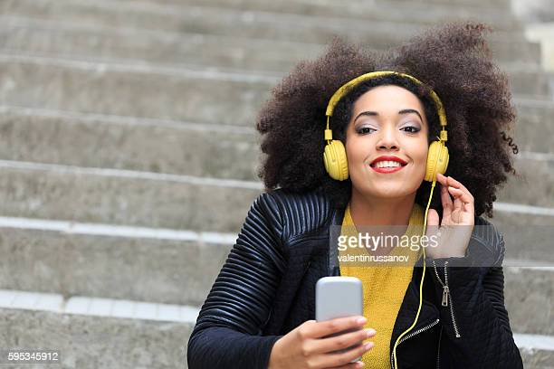 Attractive young woman sitting on stairs and listening music