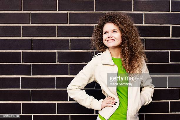 Attractive young woman smiling on the wall background