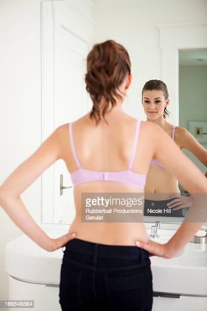 Attraente giovane donna in piedi davanti allo specchietto