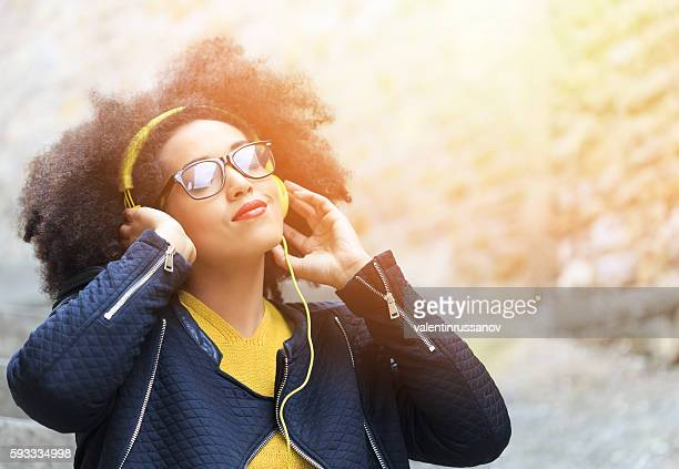 Attractive young woman standing on street and listening music