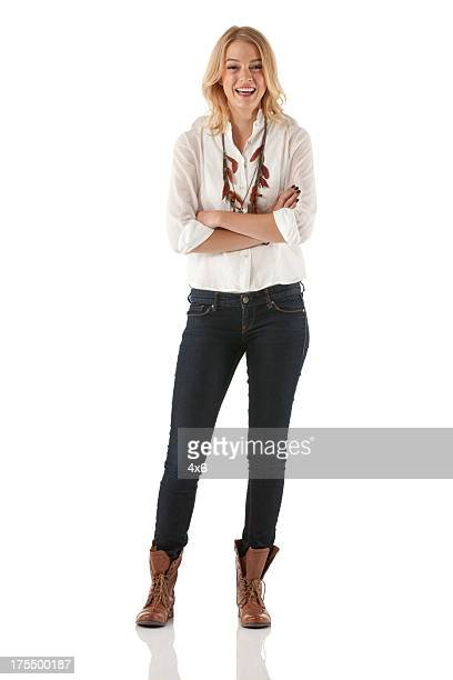 attractive young woman standing with her arms crossed - white pants stock pictures, royalty-free photos & images
