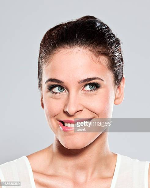 attractive young woman, studio portrait - biting lip stock pictures, royalty-free photos & images