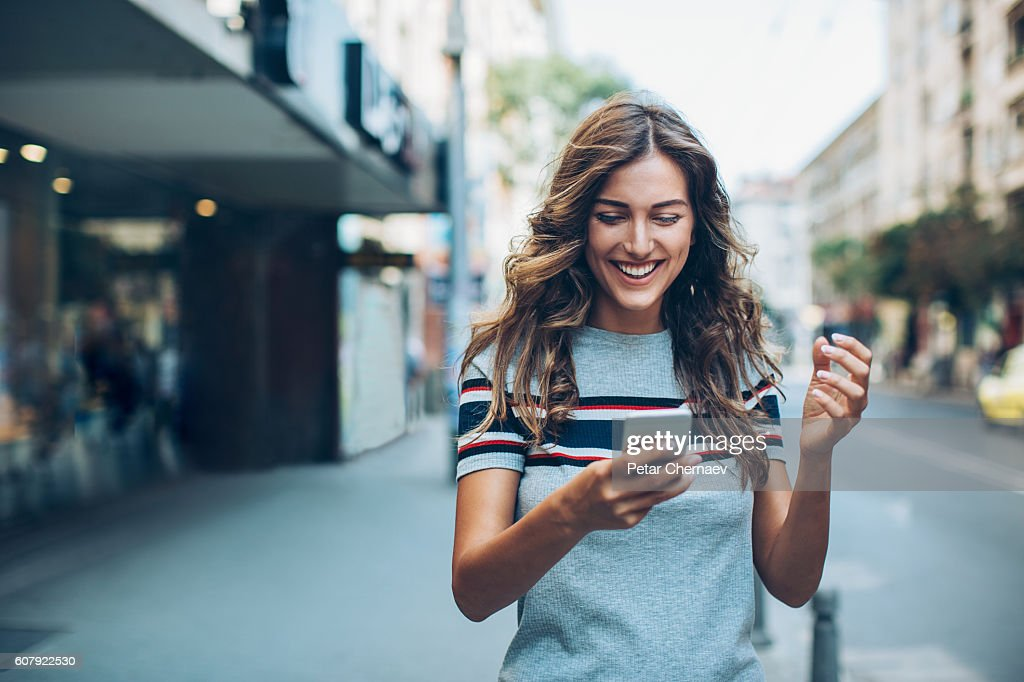 Attractive young woman texting on the street : Foto de stock