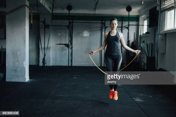 attractive young woman uses jumping rope to train - crossfit stock pictures, royalty-free photos & images