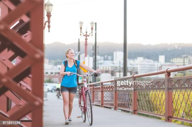 Attraktive junge Frau geht auf Brücke Gehweg Fahrrad an einem sonnigen Nachmittag