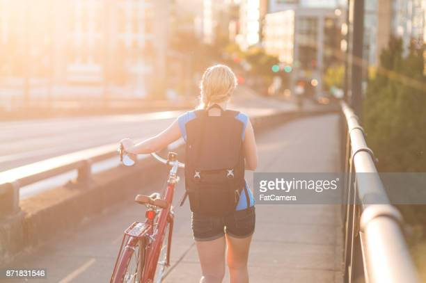 Attractive young woman walks bicycle along sidewalk on a sunny afternoon