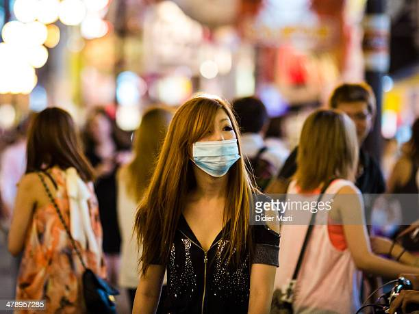 Attractive young woman wear a face mask at night in the streets of Osaka in Japan