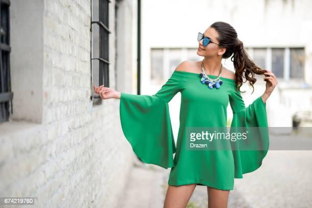 Aantrekkelijke jonge vrouw levendige groene zijden jurk dragen