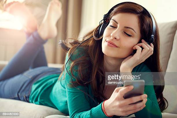attractive young woman with headphones listens music on smart ph - free download photo stock photos and pictures