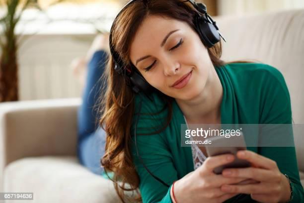 Attraktive junge Frau mit Kopfhörern hört Musik auf Smartphone