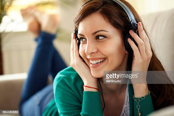 Attractive young woman with headphones listens music on smartpho