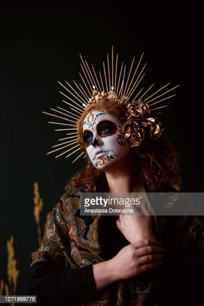 attractive young woman with sugar skull makeup on dark background - headwear stock pictures, royalty-free photos & images