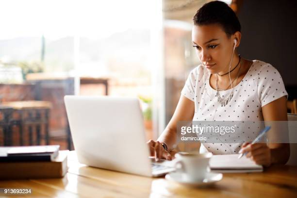attractive young woman working on laptop and taking notes at a cafe - online class stock pictures, royalty-free photos & images