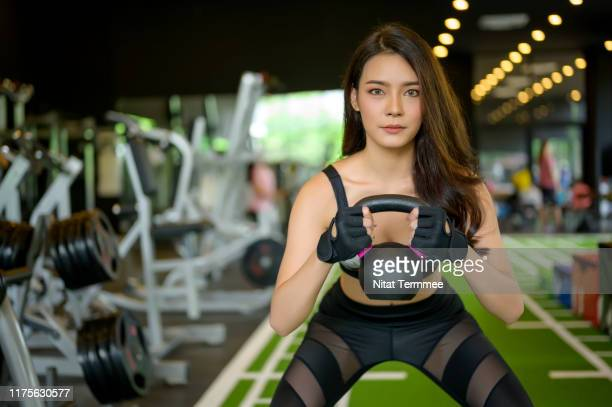 attractive young woman working out with kettlebells at a fitness gym. - トレーニンググローブ ストックフォトと画像