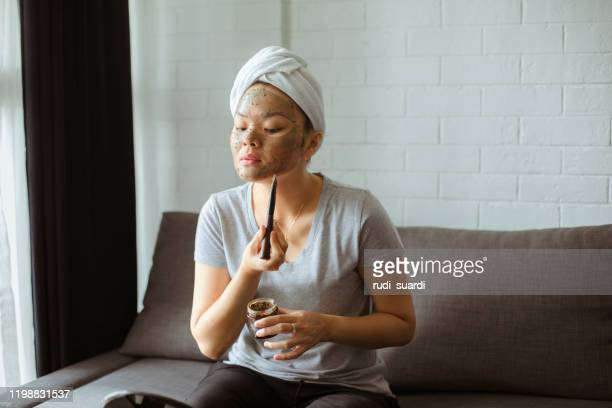attractive young woman wrapped with bath towels and cream mask on the face - face mask beauty product stock pictures, royalty-free photos & images