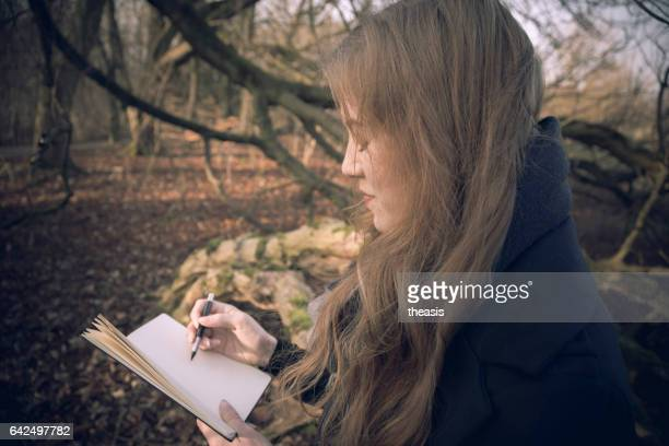 Attractive young woman writing in her journal