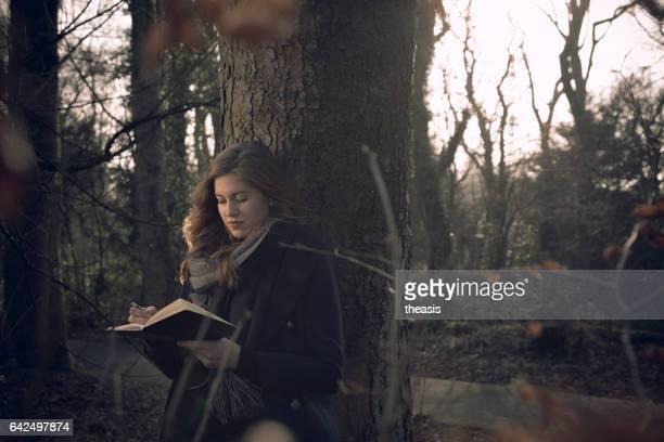 Atractiva mujer joven escribiendo en su diario