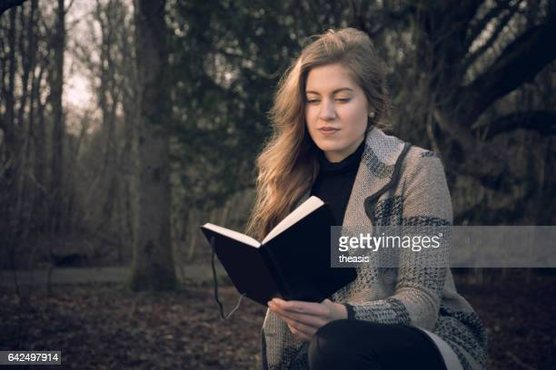 attractive young woman writing in her journal - theasis stock pictures, royalty-free photos & images
